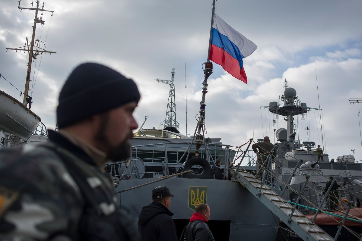 A Russian flag is raised aboard a Ukrainian navy ship that is next to the Ukrainian corvette Pridniprovya, right, in Sevastopol, Crimea, Thursday, March 20, 2014.